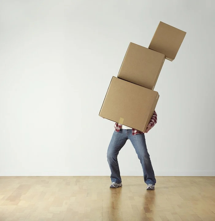 Man holding three moving boxes about to fall over