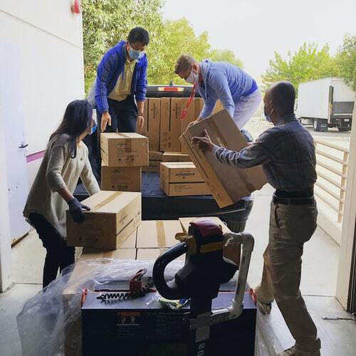 Four people packing moving boxes into a truck
